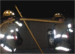 Firefighters carrying hoses